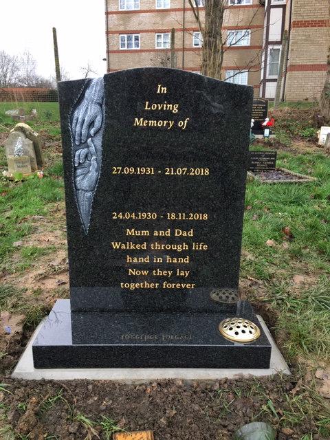 carved hands dark grey granite memorial